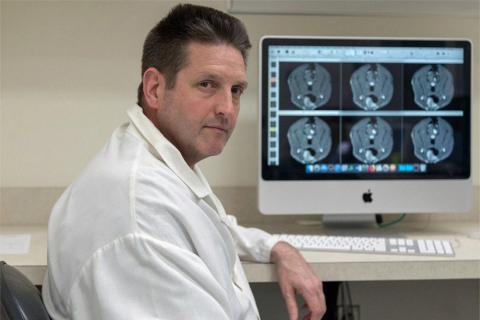 John Rossmeisl Jr. in front of MRI images
